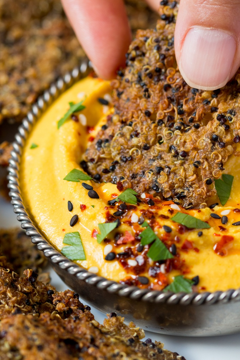 dipping quinoa cumin crackers in carrot hummus