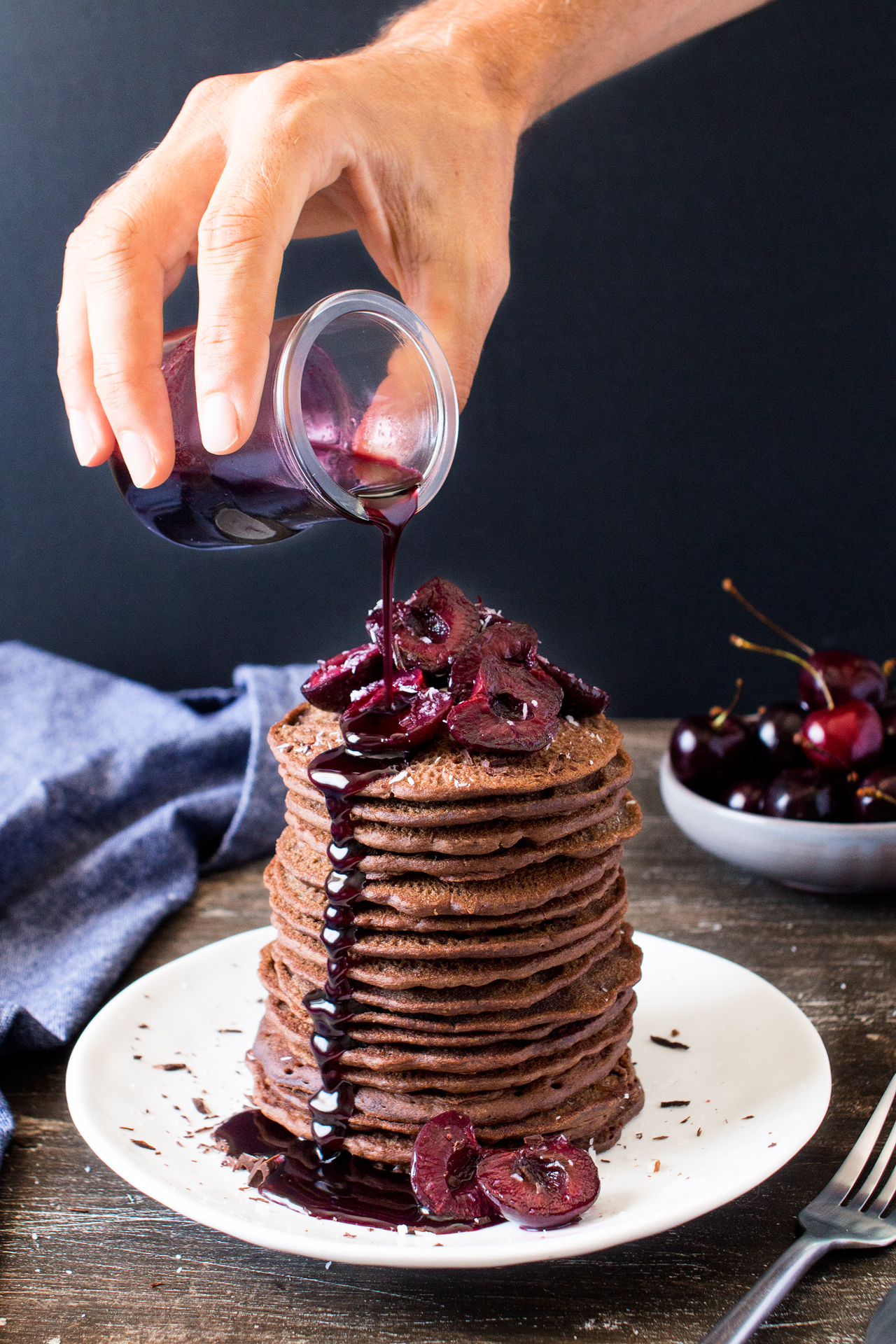 vegan chocolate pancakes with cherries pouring syrup