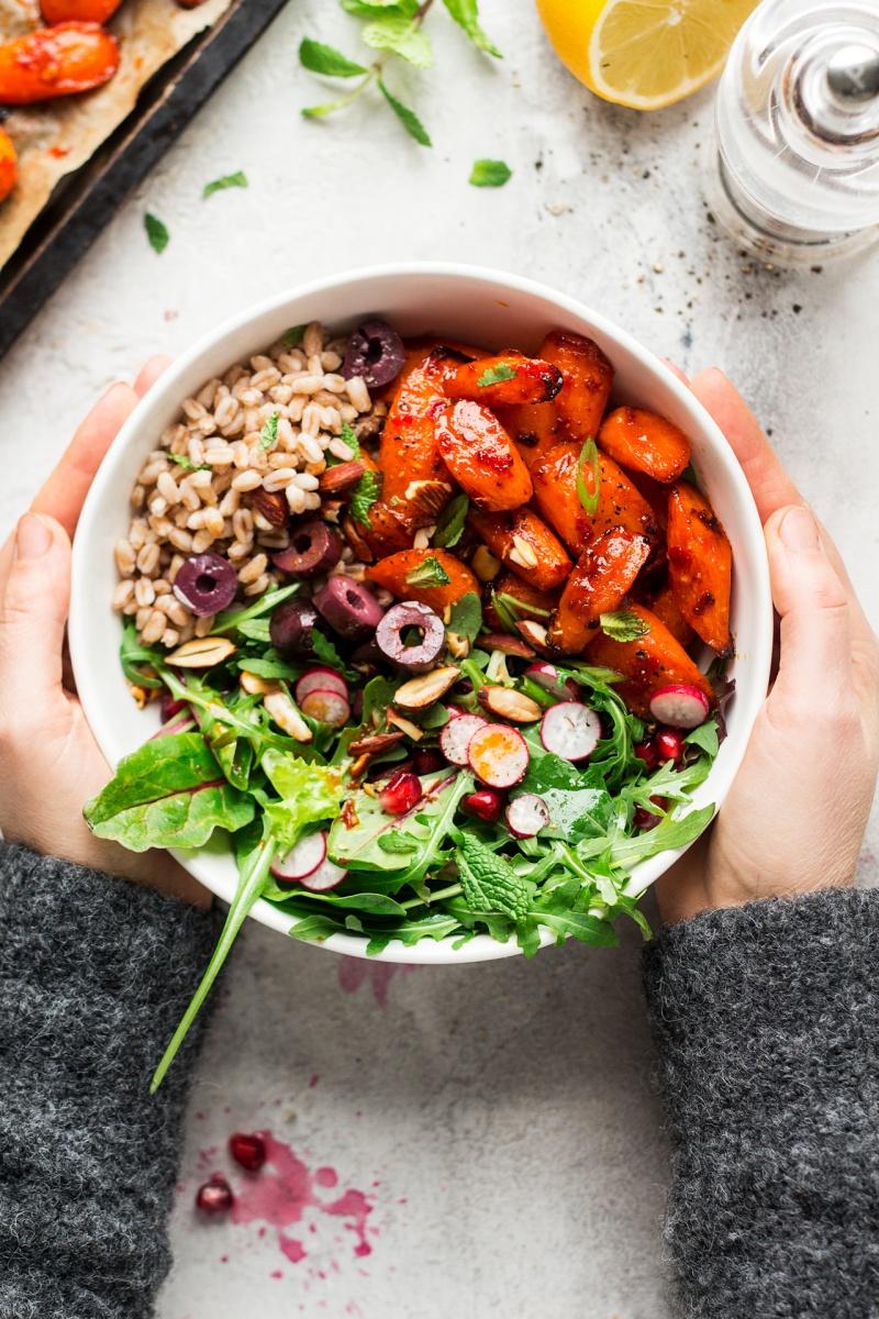 winter vegan bowl roasted carrots hands